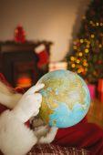 Santa pointing his finger on the globe — Foto de Stock