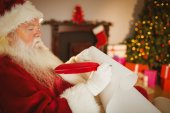 Santa claus writing his list on scroll — Stock Photo