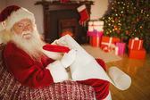Smiling santa claus writing his list on scroll — Foto de Stock