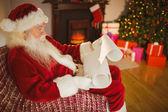 Santa claus reading his list at christmas — Foto de Stock