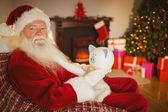 Santa claus holding piggy bank — Stock Photo