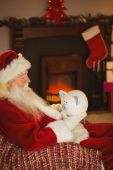 Santa claus holding piggy bank at christmas — 图库照片