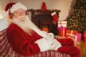 Smiling santa claus listening music — Stock Photo