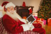Santa claus listening music and using tablet — 图库照片