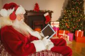Santa listening music and touching tablet — 图库照片