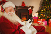 Smiling santa listening music with his smartphone — 图库照片
