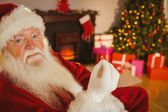 Smiling santa holding engagement ring  — Foto Stock
