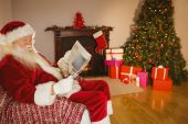 Santa claus reading newspaper on the couch — 图库照片