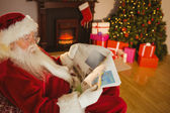 Babbo Natale legge giornale sul divano — Foto Stock