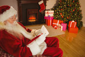 Concentrated santa writing list on scroll — Stock Photo