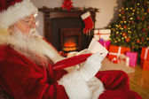Santa claus writing list on scroll — Stock Photo