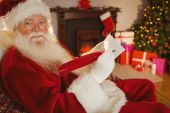 Smiling santa writing list with a quill — Stockfoto
