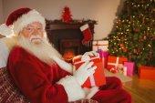 Smiling santa claus holding gift — Stock Photo