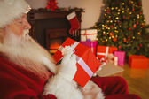 Santa claus writing on a red gift — Stockfoto