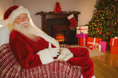 Smiling santa sitting and holding his belly  — Stockfoto