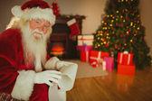 Smiling santa claus holding a scroll — Foto de Stock