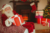Cheerful santa claus offering a gift — Stock Photo