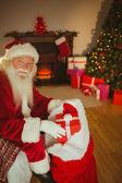 Smiling father christmas stocking presents  — Stock Photo