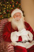 Happy santa relaxing on the armchair — Stockfoto