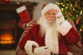 Smiling santa holding his glasses — Stock Photo