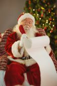Concentrated santa writing his list on a scroll — Stock Photo