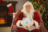 Smiling santa offering piggy bank — Foto de Stock