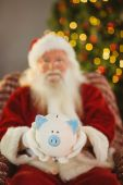 Santa claus offering piggy bank — Foto Stock