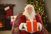 Santa claus offering a red gift — Foto Stock