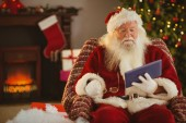 Santa holding his glasses and using tablet — Stock Photo