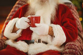 Mid section of santa holding hot drink — 图库照片
