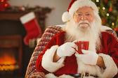 Smiling santa claus holding a mug — Stock Photo