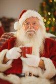 Happy santa claus holding a red mug — Stock Photo