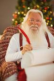 Happy santa writing list on the armchair — Stock Photo