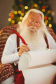 Concentrated santa writing list on the armchair — 图库照片