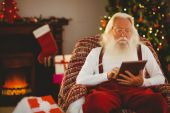 Santa claus using tablet on the armchair — 图库照片