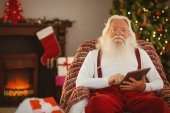 Smiling santa using tablet on the armchair — 图库照片