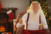 Santa holding glass of milk and plate with cookie — 图库照片