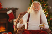 Santa holding glass of milk and plate with cookie — Foto Stock