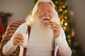 Smiling santa claus eating a cookie — 图库照片