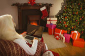 Santa sitting and using laptop on the armchair — Stock Photo