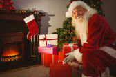 Smiling santa delivering gifts at christmas eve — Stock Photo