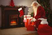 Cheerful santa delivering gifts at christmas eve — Stockfoto