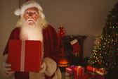 Zaskoczony Mikołaja dostarczanie świecące prezent — Zdjęcie stockowe