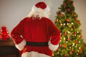 Rear view of santa standing in front of the christmas tree — Stock Photo