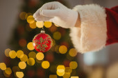 Hand of santa holding a bauble — 图库照片
