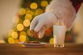 Hand of santa claus picking cookie — 图库照片
