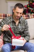 Man opening a gift on the couch at christmas — Stock Photo