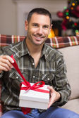 Happy man opening a gift on christmas day — Stock Photo