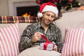 Smiling man in santa hat opening a gift — Stockfoto