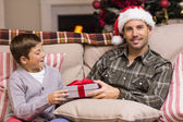 Son giving father a christmas gift on the couch — Fotografia Stock